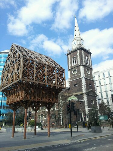 The wooden structure marks the spot of the Aldgate, one of the old gates of London