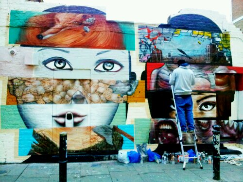 Bom.K working on the mural on Hanbury Street in November 2012