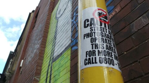 'Caution Street Art Photographers operate in this area' spotted on Redchurch Street by the Stik