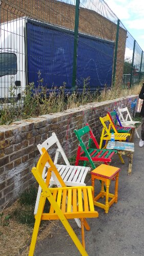 Colourful chairs on the banks of the Hertford Union Canal which separates the Wick from Fish Island