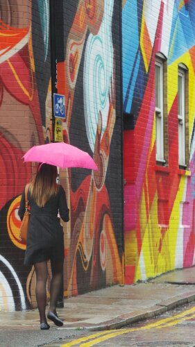 Walking up the street with a pink umbrella