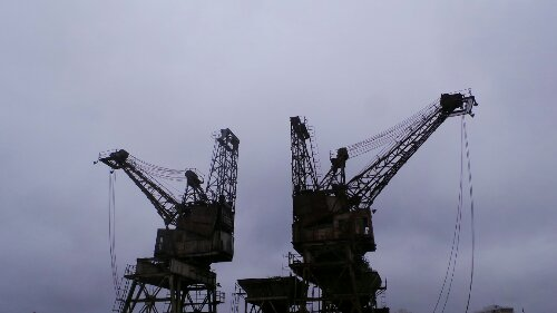 Two imposing cranes sit directly opposite the entrance to the station on the banks of the Thames