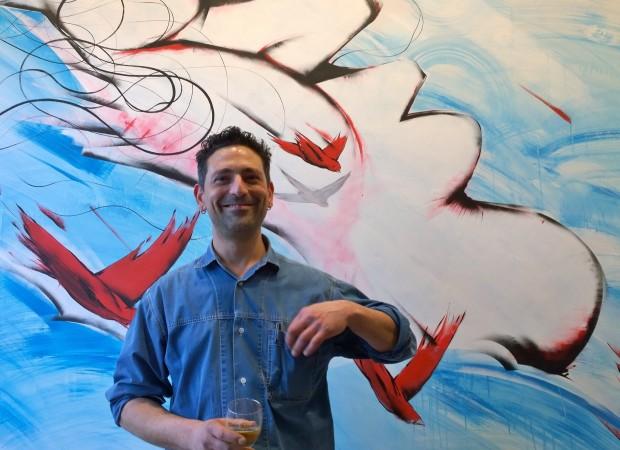 Italian artist RUN next to his artwork at the launch
