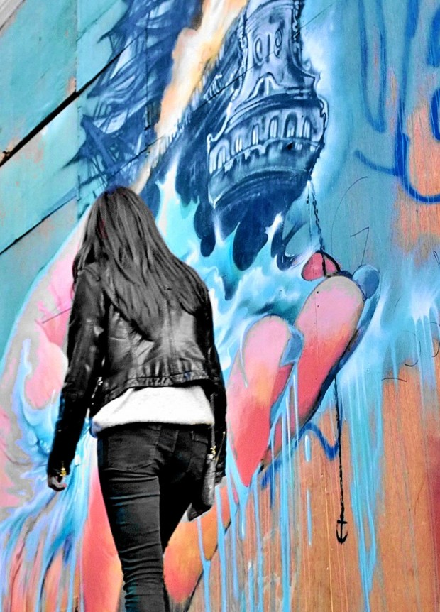 A woman walks past the impressive mural
