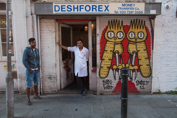 On Hanbury Street a shop owner goes about his business next to a shutter with work from Dscreet
