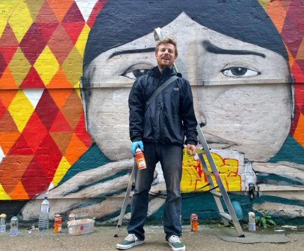 Ryan Kai next to his mural on Sclater Street