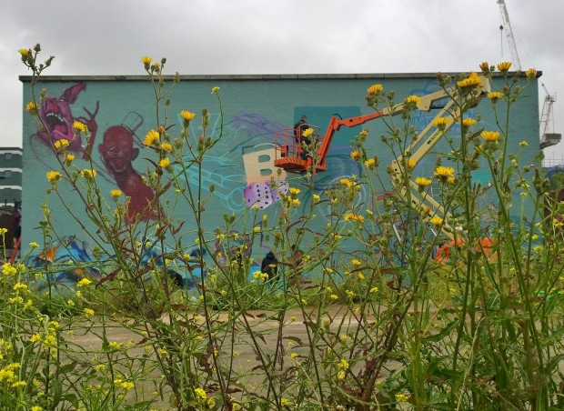 The giant wall on Pedley Street through the undergrowth