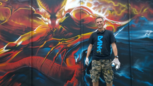 Dan Kitchener next to his unfinished mural on New Inn Yard