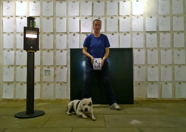 John with his dog George with his book on the pavement of a recreated Shoreditch High Street