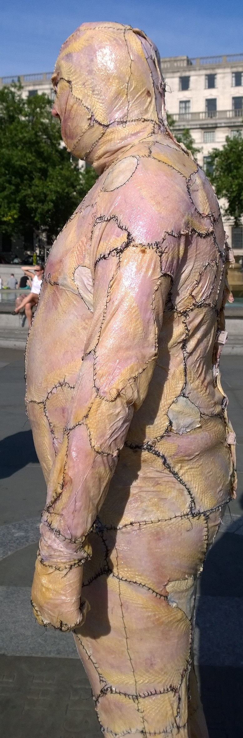 man dresses in a suit made of real chicken skin and walks