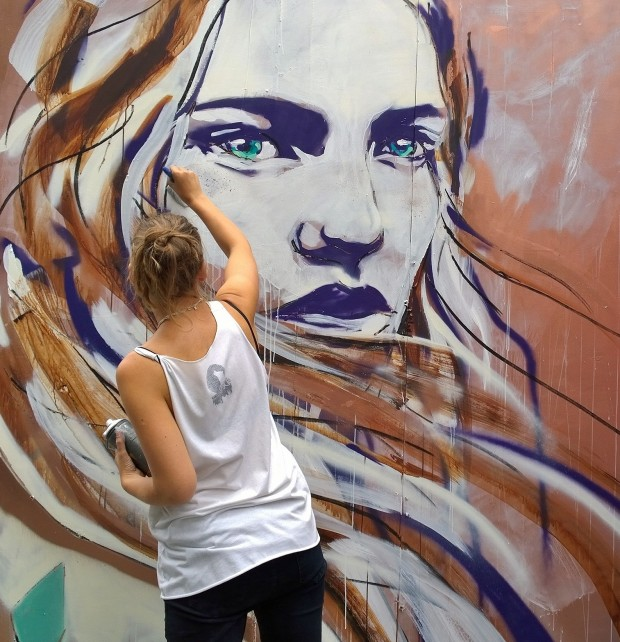 Hannah Adamaszek painting during the Whitecross Street festival.  She will be painting at the Queen of Hoxton